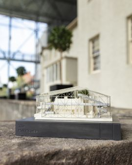 The Hill House model on a dark base, with the model on top and the silver box over it. The model is in the actual Hill House.