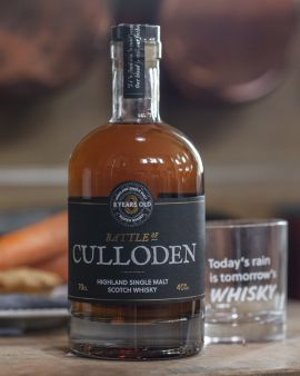A bottle of Battle of Culloden whisky in a curved shape with a label 'Highland Single Malt Scotch Whisky. 8 years old.' There is a glass behind the bottle with the etching 'Today's rain is tomorrow's whisky.'