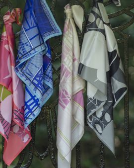 Four silk scarves in the Hill House Collection tied to a metal gate.