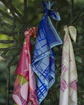 Three silk scarves in the Hill House Collection tied to a metal gate.