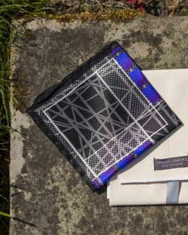 The folded black and blue silk pocket square.