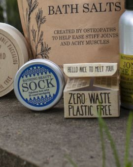 An image of the product with a label that says 'Bathing Beauty Sock: Fabulous Foot Salve'. It is next to the small box that it comes in that says 'Zero Waste Plastic Free.'
