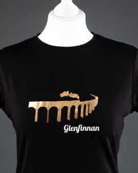 The tshirt on a dressmaker's model. It is black with a high neck and short sleeves. On the front is the Glenfinnan Viaduct with a  steam train passing over, it in gold. Underneath is written 'Glenfinnan.'