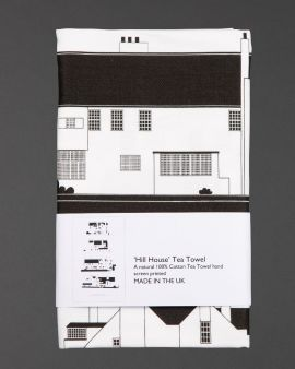 The folded tea towel that features the four elevations of the Hill House. The label says 'Hill House Tea Towel. A natural 100% Cotton Tea Towel hand screen printed. Made in the UK.'