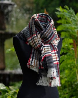 The reversible merino wool scarf  wrapped and knotted around the neck of a dressmaker's model.   It is in front of a fountain.