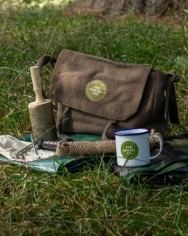 In front of a tree, the Den Kit is laid out. There is the Den Kit bag, mallet, rope, camouflage, ten and ten bag and mug.