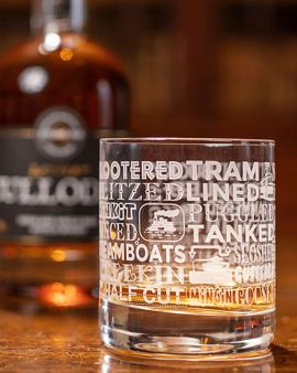 An etched crystal whisky tumbler features 29 different words for drunk: Sloshed, Puggled, Lined, Tram, Blitzed etc. There is a whisky bottle (sold separately) behind it.