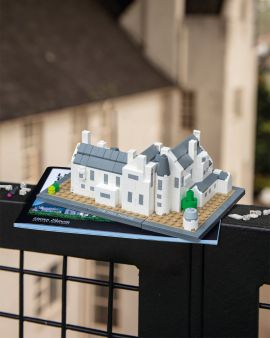 The completed Hill House with LEGO® bricks, on top of the instruction book. The actual Hill House is in the background.
