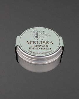 The tin of balm with labelling on top saying Melissa Beeswax Hand Balm.