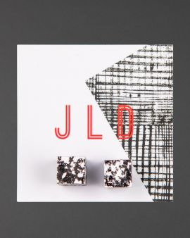 black and white cube stud earrings on a backing card