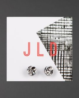 circular stud earrings in black and white on backing card