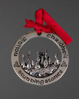 A round silver-plated decoration with standing stones in the middle. It says 'Nollaig Chridheil' or 'Merry Christmas' in Scottish Gaelic and down the bottom 'Standing Stones'. It has a red ribbon to hang.