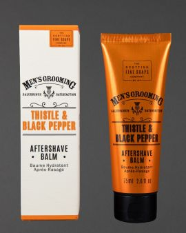 A tube of Thistle and Black Pepper Aftershave Balm next to the box it comes in.