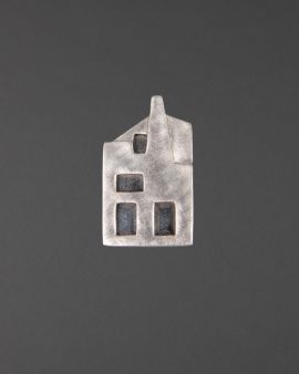 A small silver brooch with black windows depicting the west elevation of the Hill House.