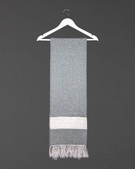 the hamman throw in grey hanging from a white coat hanger