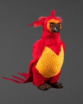 A small toy of Hawkes the phoenix in red, yellow and with long feathers.