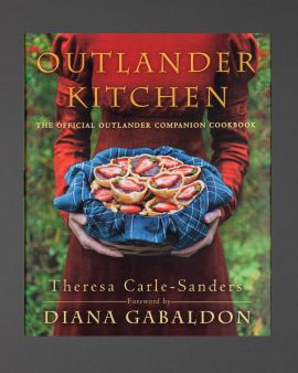 The cover of the book 'Outlander Kitchen.' There is a picture of a women in a red dress, in her hands is a basket with a tartan cloth, filled with a homemade jam tart.