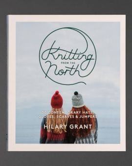 The cover of the book which shows the backs of two women looking out to sea, they wear woolen hats and jumpers.