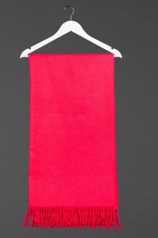 Hot pink cashmere silk scarf  hanging from a coathanger.