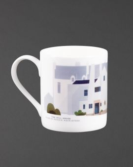 The mug with a curved handle. The mug has the west elevation of the Hill House on it. Underneath it says 'The Hill House Charles Rennie Mackintosh.'