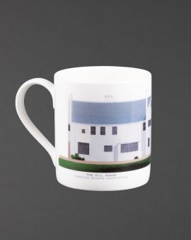 The mug with a curved handle. The mug has the south elevation of the Hill House on it. Underneath it says 'The Hill House Charles Rennie Mackintosh.'