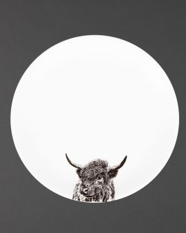 A round plate with a design of a Highland cow at the bottom.