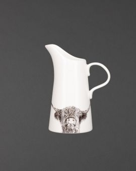 A ceramic jug with an illustration of a Highland Cow at the bottom.