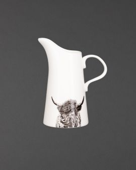A ceramic jug with a pointed spout and curved handle. There is an illustration of a Highland Cow at the bottom.