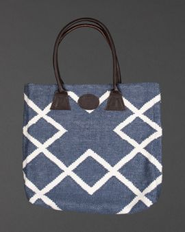 The front of the navy recycled bag with a white design on top. The top of bag has two straps.
