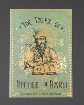 The front cover of 'The Tales of Beedle the Bard' with the Bard writing with a quill.