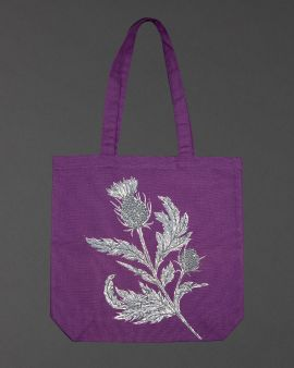 A large purple tote bag with a long strap, and thistle pattern in the centre.