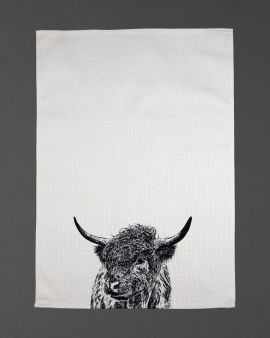 A tea towel with an image of a Highland cow at the bottom in the middle.
