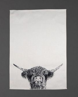 A tea towel with an illustration of a Highland Cow at the bottom.