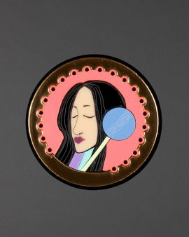 A large round brooch with two round background panels. It features a woman's face.