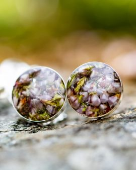 culloden heather earrings, shown on a stone wall