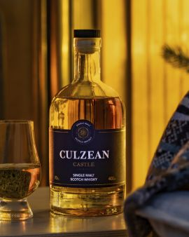 culzean whisky bottle set on a table with a half filled glass beside it
