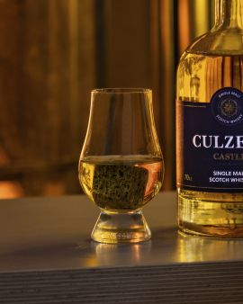the glencairn whisky glass, shown with a granite ice cube in it and half filled with culzean whisky
