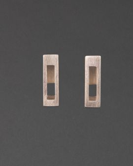 Two silver stud earrings that are small and rectangular. There is a similar shape cut out of the middle.