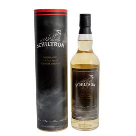 The bottle of Schiltron whisky next to the round packing it comes in.