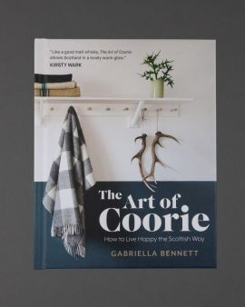 The cover of the Art Of Coorie: How to Live Happy the Scottish Way by Gabriella Bennett. There is a quote 'Like a good malt whisky, The Art of Corrie shines Scotland in a lovely warm glow.'