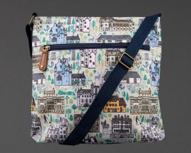 front of buildings of the national trust for scotland cross body bag, showing strap across the front of bag