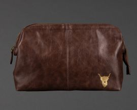 front of chocolate brown highland cow wash bag, showing gold highland cow emblem