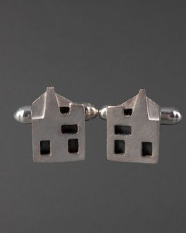 two silver cufflinks in the shape of the hill house