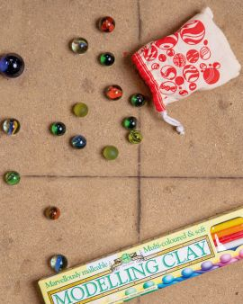 A drawstring bag for storage and a selection of marbles on the ground.